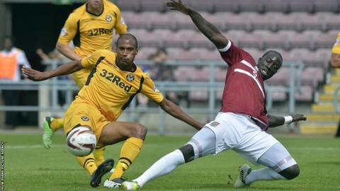 Newport County striker Chris Zebroski is tackled by Northampton's Kevin Amankwahh during the League Two game at Sixfields.