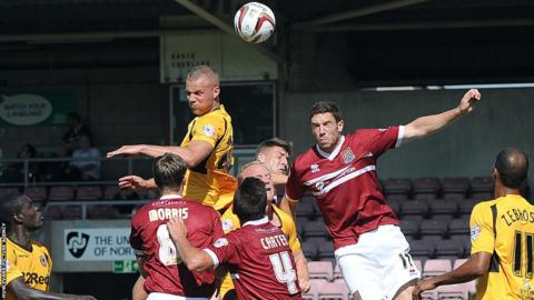 Defender Harry Worley wins an aerial battle during Newport's game at Northampton Town.