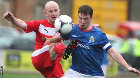 Cliftonville's Ryan Catney challenges Linfield midfielder Jamie Mulgrew