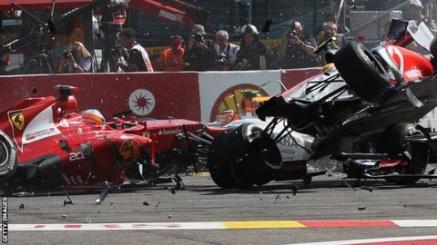 Fernando Alonso (L) of Spain and Ferrari and Lewis Hamilton (R) of Great Britain and McLaren collide and crash out at the first corner at the start of the 2012 Belgian Grand Prix