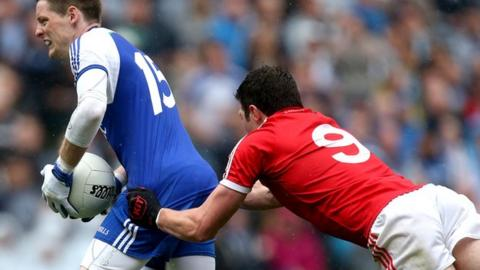 Monaghan's Conor McManus is tackled by Sean Cavanagh of Tyrone