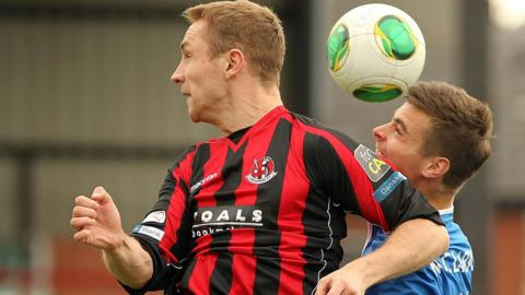 Crusaders striker Timmy Adamson competes for a high ball with Linfield defender Matthew Clarke