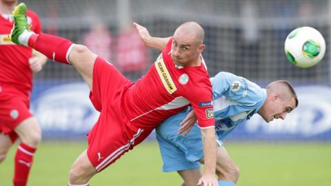 Barry Johnston of Cliftonville goes for the ball with Warrenpoint's Ruairi Devlin at Stangmore Park