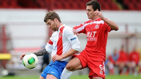 Ards midfielder Ryan Henderson attempts to hold off the challenge of Portadown defender Chris Ramsey