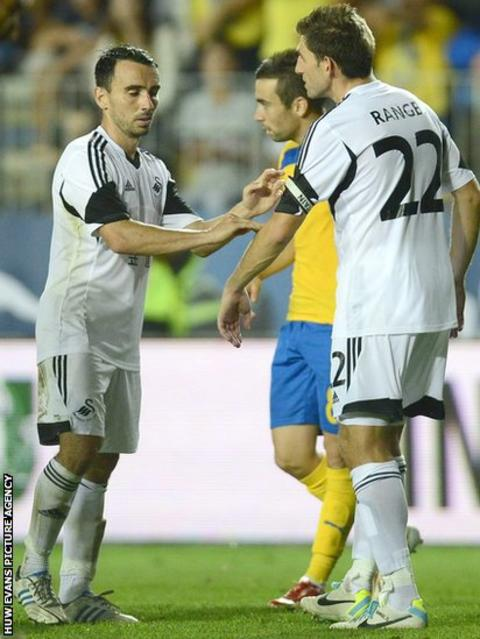 Leon Britton hands over the captain's armband to Angel Rangel after being sent off
