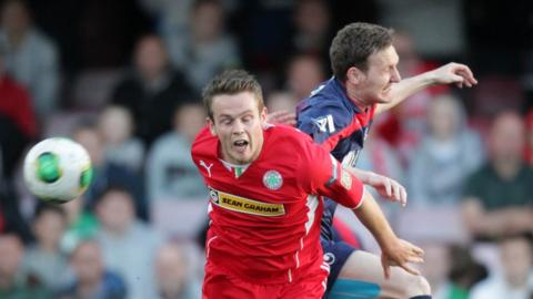 Jaimie McGovern and Gary Twigg challenge for the ball as Portadown defeat champions Cliftonville at Solitude