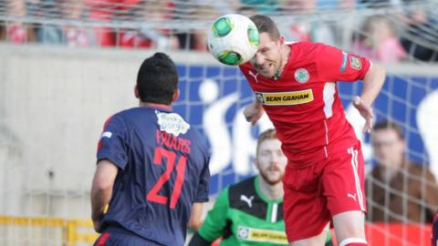 Cliftonville's Marc Smyth heads the ball as Portadown defender Emmett Friars looks on