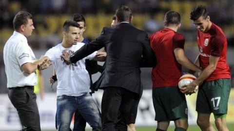 Officials usher away two Macedonian fans who entered the pitch during the interval to embrace Wales substitute Gareth Bale.