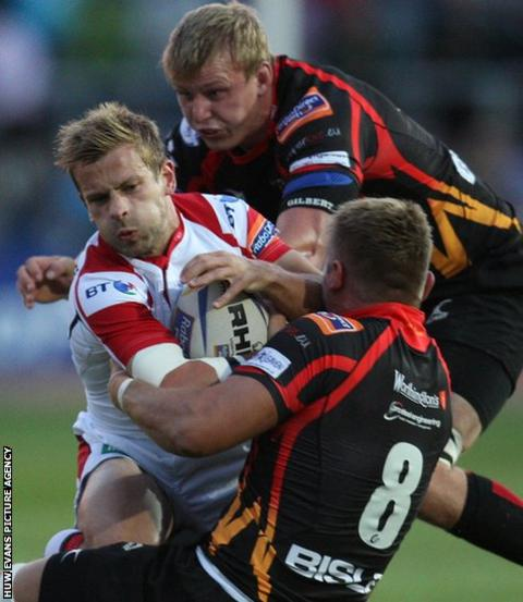 Ulster's Paul Marshall is tackled by Lewis Evans in Newport Gwent Dragons' first game of the Pro12 season at Rodney Parade.
