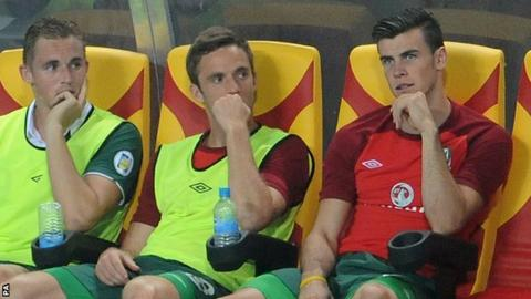 Gareth Bale (right) looks on from the Wales bench as they fall to defeat in Macedonia