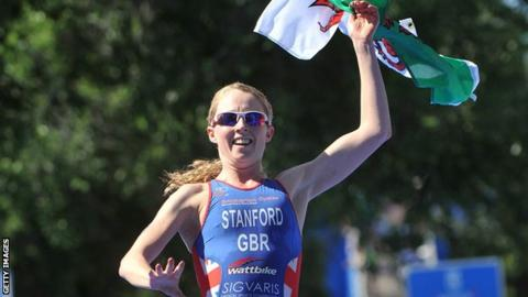 Non Stanford waves a Welsh flag as she crosses the line to win the ITU world series triathlon in Madrid in 2013