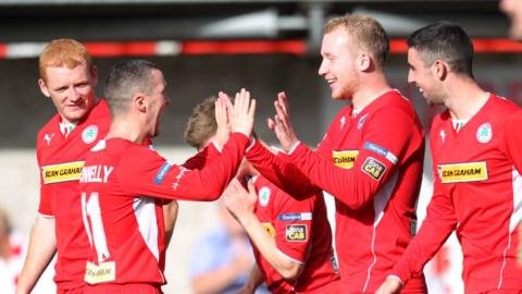 Martin Donnelly celebrates one of Cliftonville's goals in their 4-1 win over Glentoran with Liam Boyce