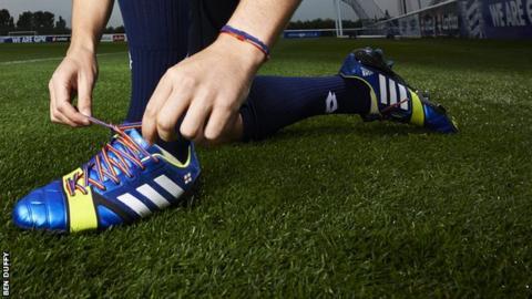 Footballer lacing up