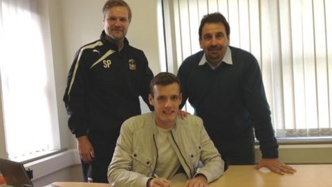 Stuart Urqhart signs for Coventry, watched by boss Steven Pressley and development director Steve Waggott