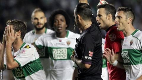 Elche's players protest as referee Cesar Muniz shows a yellow card to Ruben Perez