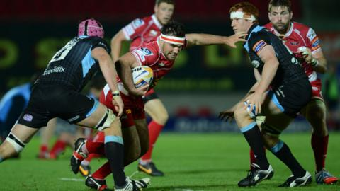 Scarlets hooker Emyr Phillips runs into Glasgow defenders Tim Swinson and Rob Harley during the Pro12 match at Parc y Scarlets that ended in a 17-12 win for Glasgow