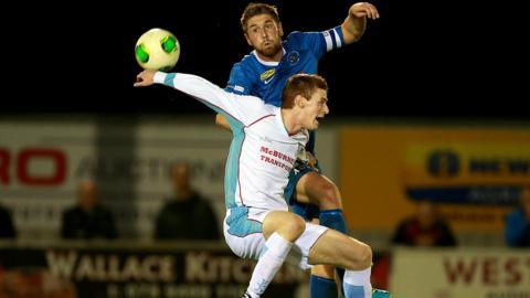 Ballinamallard United skipper Mark Stafford competes for a high ball with Ballymena United opponent Aaron Stewart