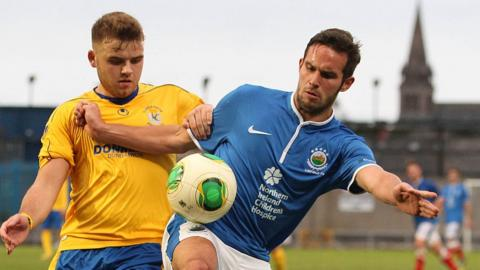 Matt Hazley challenges Linfield's Andrew Waterworth, who scored both goals in his side's 2-0 victory over Dungannon Swifts