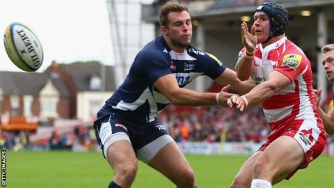 Gloucester's Rob Cook (right) passes as Andy Forsyth (L) Sale closes in
