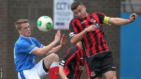 Linfield's Aaron Burns competes against Crusaders skipper Colin Coates in last month's Premiership clash