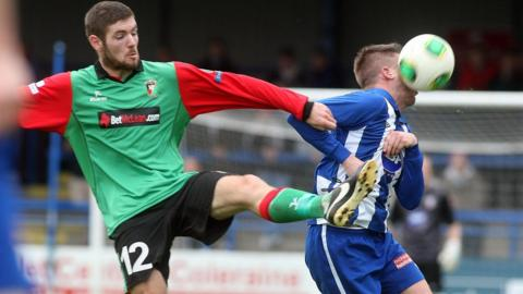 Glentoran's Mark Clarke challenges as the ball strikes Aaron Canning of Coleraine at the Showgrounds