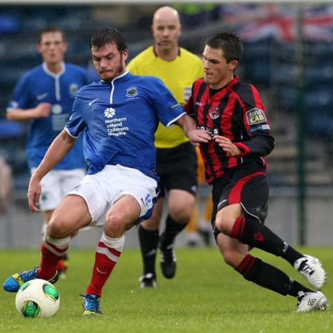 Linfield's Philip Lowry in possession against Craig McClean of Crusaders during the 0-0 draw at Windsor Park