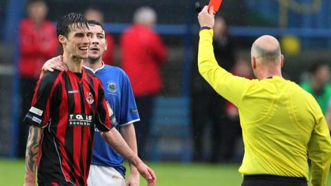 Referee Mark Courtney shows the red car to Crusaders midfielder Declan Caddell with Linfield skipper Michael Gault looking on