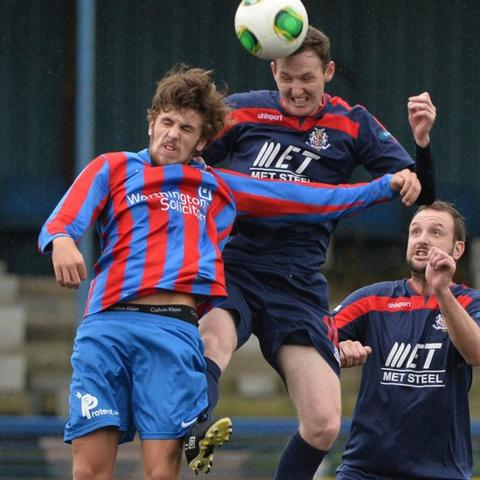 Steven McCullough of Ards is beaten in the air by Portadown's Gary Twigg at Clandeboye Park