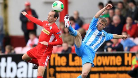 Cliftonville's Ronan Scannell gets to the ball ahead of Warrenpoint's Liam Bagnall during the 1-1 draw at Solitude