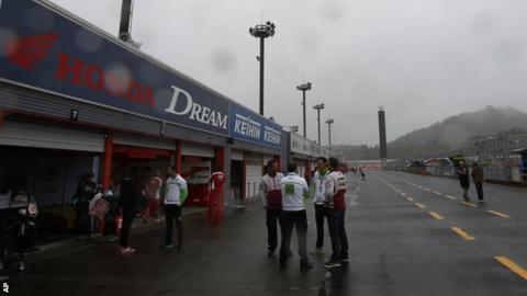 Team members talk in the pit lane after practice was cancelled due to weather during the MotoGP Japanese Grand Prix at the Twin Ring Motegi circuit