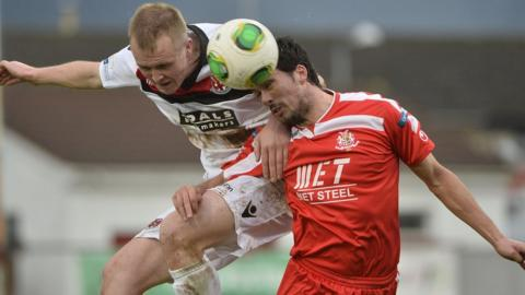 Jordan Owens of Crusaders competes against Portadown defender Emmett Friars during the match at Shamrock Park