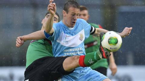 Glentoran's Jimmy Callacher stretches in an attempt to take the ball away from Ballymena United skipper Allan Jenkins