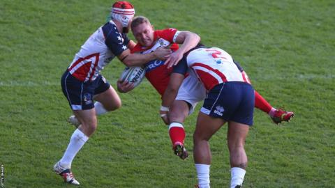 Christiaan Roets is upended by USA tacklers Craig Priestly and Bureta Faraimo during the Rugby League World Cup Group D game in Wrexham but later puts Wales ahead with the first try