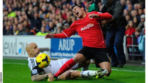 Cardiff City's Gary Medel grimaces as Swansea's Jonjo Shelvey gets in an early tackle in the south Wales derby