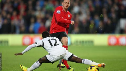 Swansea's Nathan Dyer stretches to block a pass from Andrew Taylor of Cardiff