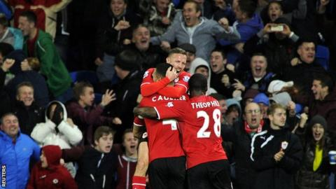 Cardiff match-winner Steven Caulker is mobbed by his team-mates in front of delighted Bluebirds fans
