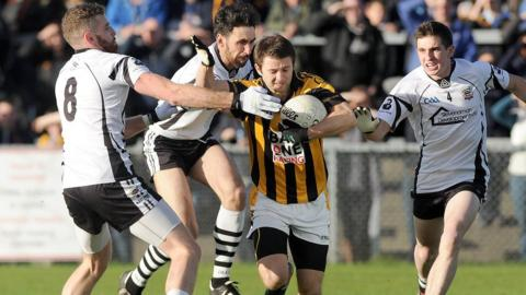 Three Kilcoo players attempt to halt the run of Crossmaglen's Kyle Brennan at Pairc Esler
