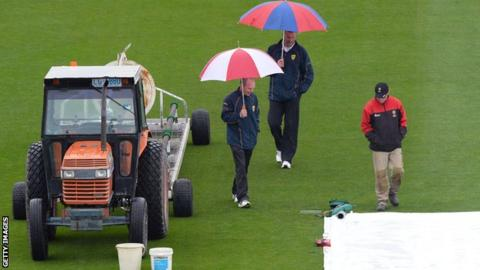 Umpires inspect the outfield