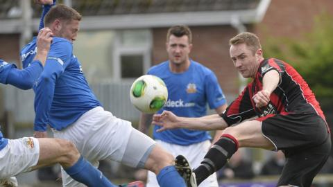 Kris Lindsay blocks a shot from Timmy Adamson as Gareth McKeown looks on at Mourneview Park