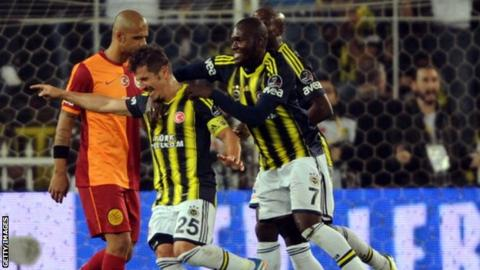 Fenerbahce's Emre Belozoglu celebrates with team-mates after scoring against Galatasaray