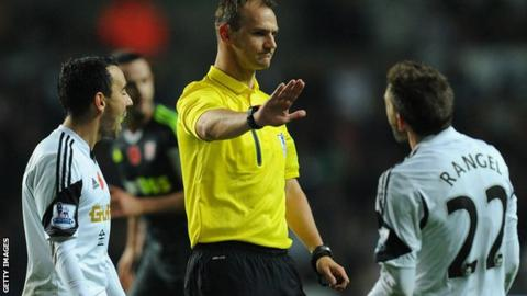 Referee David Madley brushes away the protests of Swansea City players Leon Briton and Angel Rangel