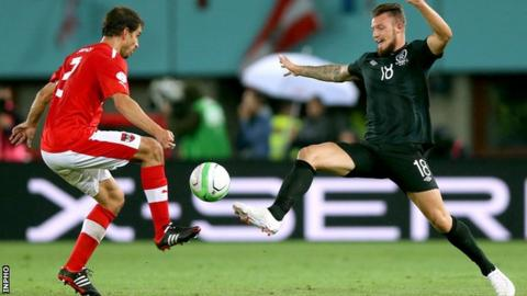 Austria's Gyorgy Garics competes for the ball with Anthony Pilkington