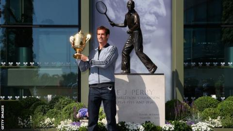Andy Murray poses with the Wimbledon Men's Singles Trophy next to the Fred Perry statue