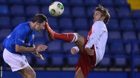 David Rainey of Glenavon goes in bravely against Steven McCullough of Ards