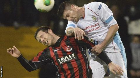Sean Cleary of Crusaders is beaten to the high ball by Ballymena's Davy Munster