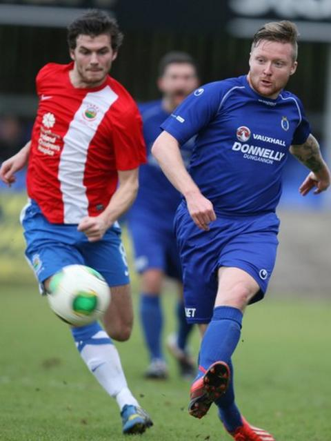 Matt Hazley gets to the ball ahead of Linfield opponent Philip Lowry during the match at Stangmore Park which Dungannon Swifts won 1-0