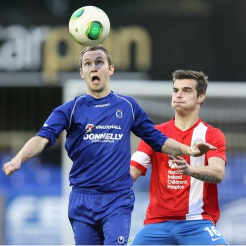 David McCullough of Dungannon Swifts heads the ball as Linfield defender Matthew Clarke moves in to challenge