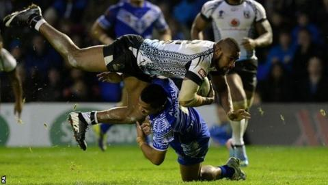 Fiji's Marika Koroibe is tackled by Samoa's Anthony Milford