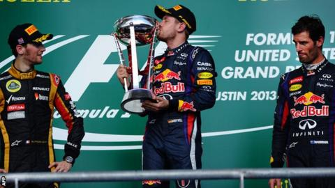 Sebastian Vettel celebrates alongside second-placed Lotus driver Romain Grosjean and his teammate third-placed Mark Webber