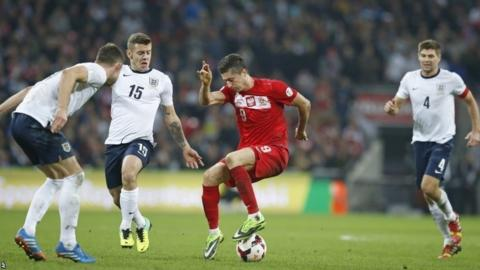 England's Gary Cahill, left, Jack Wilshere and Steven Gerrard, right, close down Poland's Robert Lewandowski during the World Cup Group H qualification match